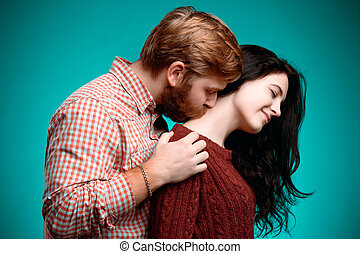 Young man and woman kissing on blue studio background