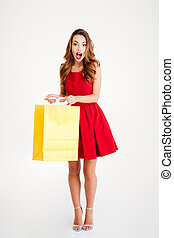 Portrait of a cheerful young woman holding shopping bag