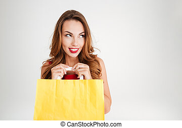 Charming pretty woman holding yellow shopping bag and...