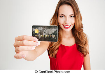 Happy attractive young woman holding and showing credit card...