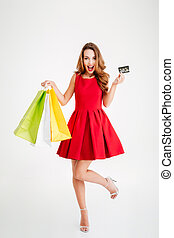 Portrait of a woman holding shopping bags and bank card -...