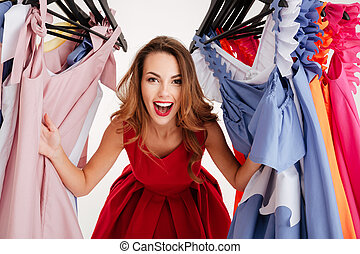 Woman shopper peeking out through clothing in clothes rack -...