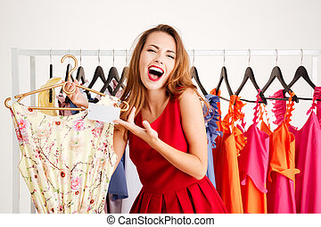 Lovely young woman costumer laughing at price in shop -...