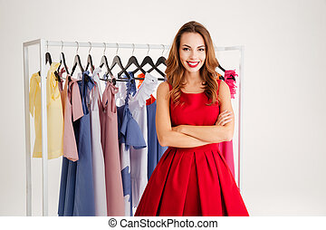 Pretty woman standing at the rack with colorful clothes -...