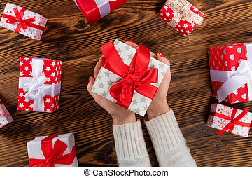 Woman holding Christmas present on wooden table background