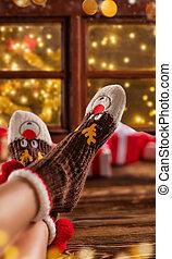 Woman feet in woollen socks, blur Christmas background