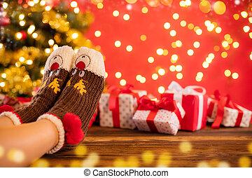 Woman feet in woollen socks, blur Christmas background -...