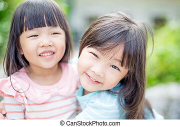 girls smile happily in park