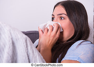 Young woman lying ill on the couch at home