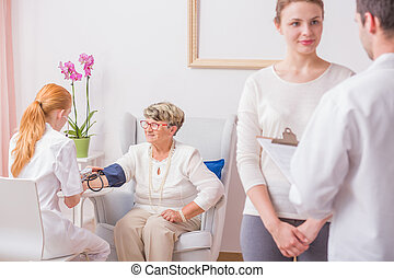 Nurse checking blood pressure for elderly lady while her...