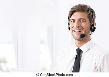 Smiling call-center employee with headphones - Smiling young...
