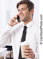 Elegant man with mobile and coffee - Elegant man talking on...