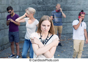 Girl among people with phones - Sad girl standing among...