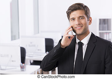 Elegant businessman talking on the phone - Working area with...
