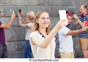 Girl taking selfie with her modern phone