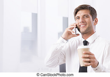 Employee talking on mobile with coffee - Work office area...