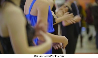 People applaud synchronously to the beat - close-up of clapping hands of sitting people on dancing event