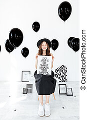 Cheerful girl with white board over black balloons bakground...