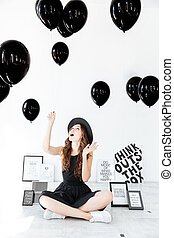 Woman sitting with legs crossed and looking up at balloons -...