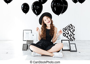 Cheerful girl sitting with legs crossed and holding black...