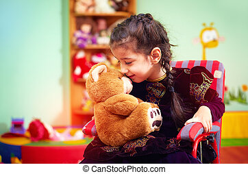cute little girl in wheelchair hugging plush bear in...