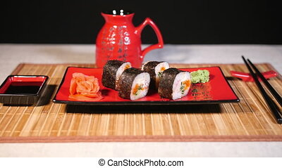 Japanese sushi on red plate with chopsticks on bamboo...