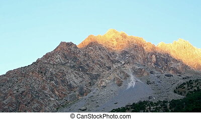 Mountain in the light of the rising sun. Time Lapse. Pamir, Tajikistan
