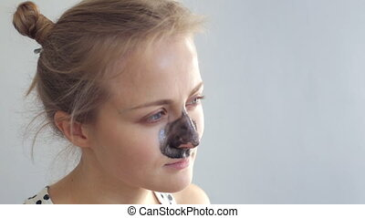 Young woman with black mask on her nose. Blackhead removing
