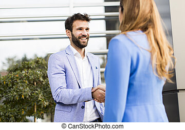 Handshaking - Young business people shake hands in front of...