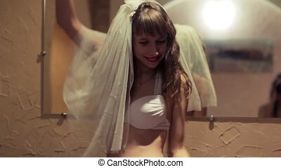 Girls in bathing suits and a veil dancing on the eve of the wedding bachelorette party