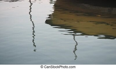 Reflection of boat on water surface. Yellow boat reflected...