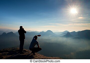 Two friends. Hiker thinking and photo enthusiast takes...