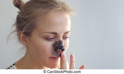 Black nose facial mask. Young woman cleaning nose pores
