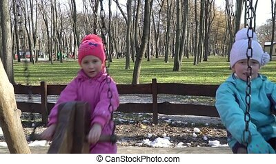 Girls ride on a swing - Two little girls in the late autumn...
