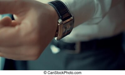 The man in the white shirt putting watch - Male businessman...