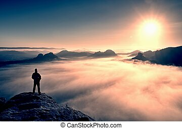 Man stands on peak of sandstone rock in Saxony Switzerland...
