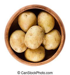 Raw mini potatoes in wooden bowl over white - Raw mini...