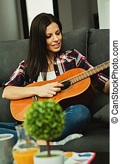 Brunette woman at home playing the guitar