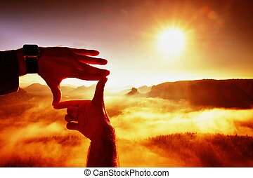 Close up of hands making frame gesture. Blue misty valley bellow rocky peak. Sunny spring daybreak in misty rocky mountains.