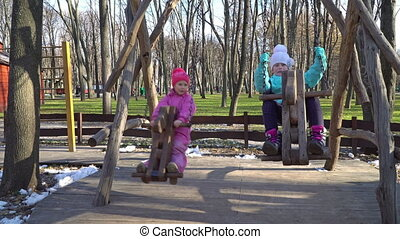Two children riding on a horse swings