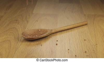 Grain of buckwheat falling on the wooden spoon lying on a...