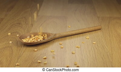Grain of pea falling on the wooden spoon lying on a wooden...