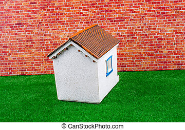 House model on a red brick background with green grass