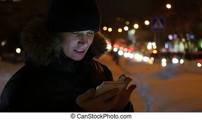 Man sms texting using app on smartphone at night in city, winter time.