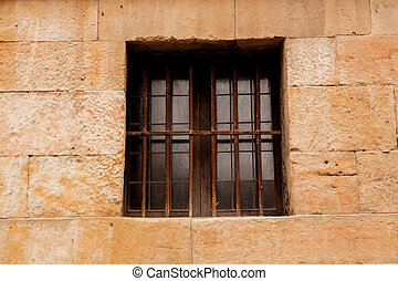 Window with rusty grilles on a stone facade - Window with...