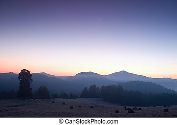 Picturesque misty and cold sunrise in landscape. First...