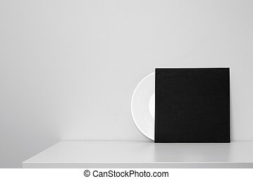 white vinyl record in black paper case put on table and...