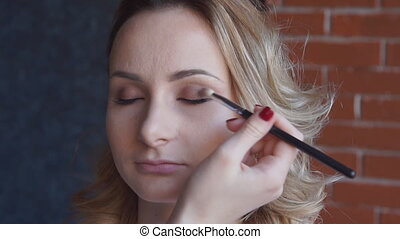 Professional makeup artist putting cosmetics on model face.