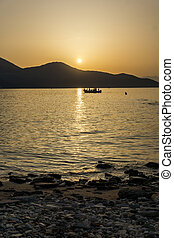 Sunset seascape with old boat in the sea of Thassos town,...
