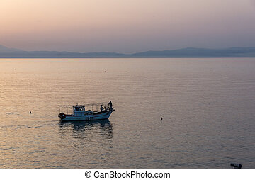 Amazing Sunset view with fishing boat in the sea of Thassos...